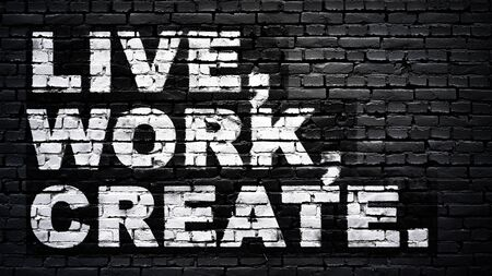 Live, work, create, motivation slogan, white text on black brick wall Foto de archivo