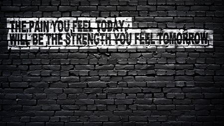 The pain you feel today, will be the strength you feel tomorrow, motivation and inspiration slogan, white text on black brick wall