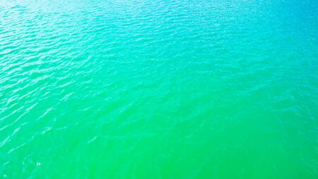 Summer background - turquoise water surface with small waves in the sun light