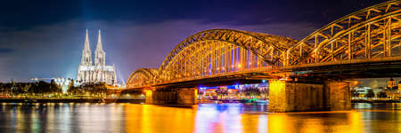 Panorama of Cologne by night, with Hohenzollern Bridge over the Rhine River and Cologne Cathedral
