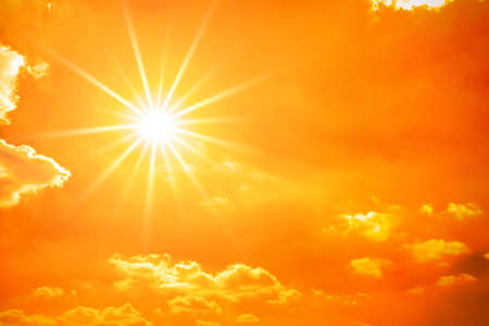 Hot summer or heat wave background, orange sky with clouds and glowing sun 스톡 콘텐츠