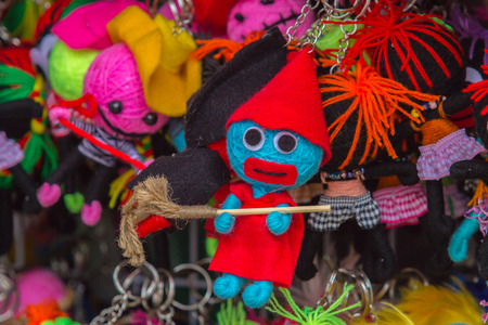 coser: A little witch doll yarn with red hat carrying broom.