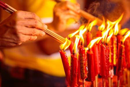 temple burn: Hand and the fire candle and the burning stick , burning candle and burning incense.