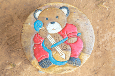 carve: Bear carve on wooden chair.