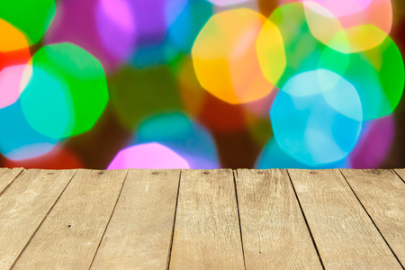 colorful light display: Empty wooden table or plank with colorful bokeh of light from building on background for product display.