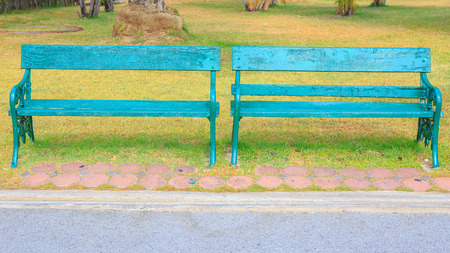 garden lawn: Two green wooden chair in the public park.