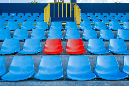 Double or two red seat or bench in the middle or center of blue chair in the football or soccer stadium.