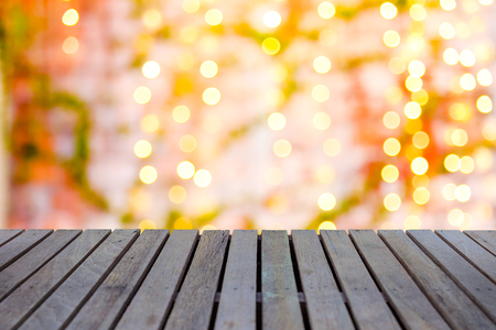 Empty wooden table or plank with bokeh from hanging electric light with brick wall and green ivy plant on background for product display. Stock Photo