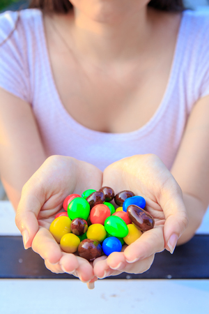 Colorful chocolate candies on hand of pretty women or girl.