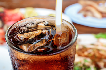 Cola in glass with ice cubes with food in the background. Banco de Imagens