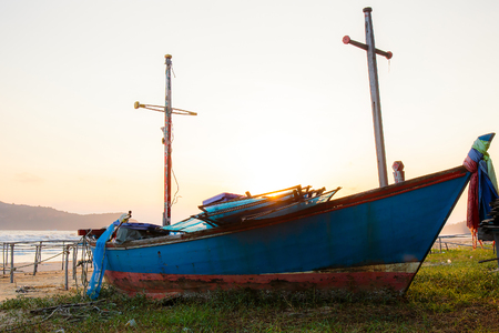 Old or abandon fisher man boat or ship on the sea beach with sunlight of sunrise on the morning. Stock Photo