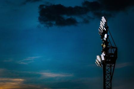 Spotlight pole tower at night of football or soccer stadium.