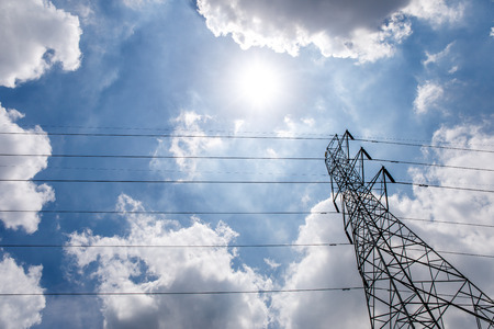 High voltage tower electric pole and wire with blue sky clouds and sun light.