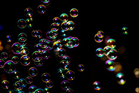 Abstract image of soap bubbles from the bubble blower in dark or black background.