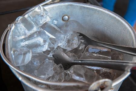 cubitos de hielo en un recipiente o balde de acero inoxidable. Foto de archivo