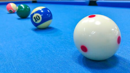 Focus on white ball of pool snooker on the blue table. Archivio Fotografico - 137052194