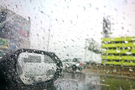 Road view through side car window mirror or rear view back with rain drops. Imagens