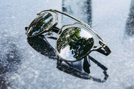 glasses with reflection of green tree leaf. Archivio Fotografico