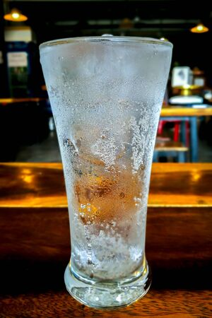 Soda water or cola with ice in glass on wooden table.