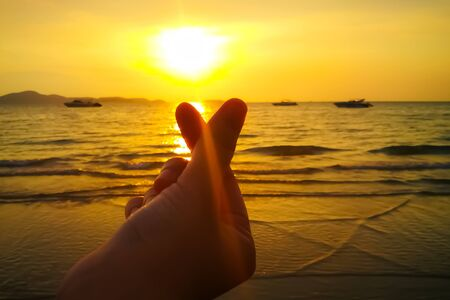 Mini heart finger hand of girl or women with sunset on the sea beach with boat and island on the background. Archivio Fotografico