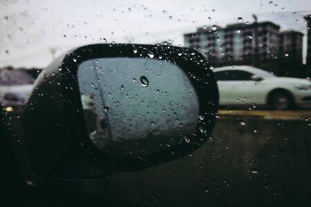 Road view through side car window mirror or rear view back with rain drops. Archivio Fotografico