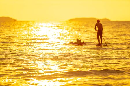 Selective focused on surface water of sea or ocean at the sunset or evening time with blurry fisher man on the surf board in color of gold or yellow golden tone. Archivio Fotografico