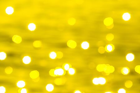 Bokeh light of sun or abstract image of surface water of sea or ocean at sunset time with gold or yellow golden light tone. Archivio Fotografico