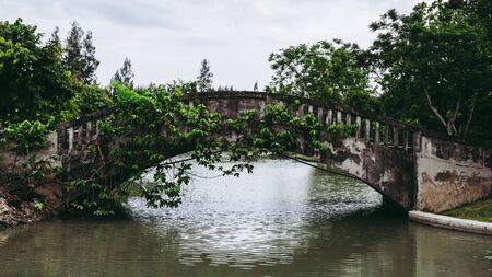 Old vintage concrete bridge over the lake or pond water in public park.