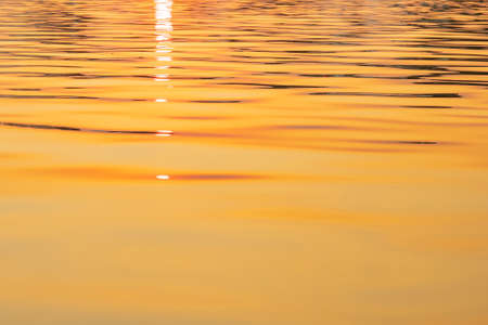 Abstract photo of surface water of sea or ocean at sunset time with golden light tone.