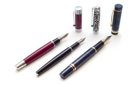 three old pen with caps over white background