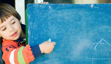 boy playing and painting on a blackboard photo