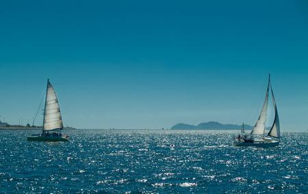 sailing ships with sun behind