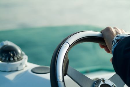 a hand with a steering wheel rudder Stock Photo