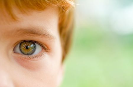 closeup of a boys eyes with the photographer reflected on the iris Stock Photo