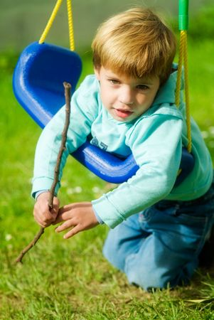 boy with funny face playing in a swing Stock Photo