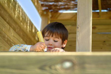 boy writing in a wood house