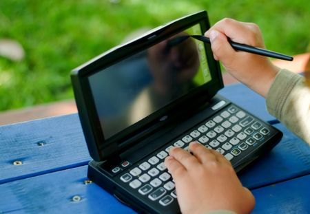 child writing an typing on a PDA
