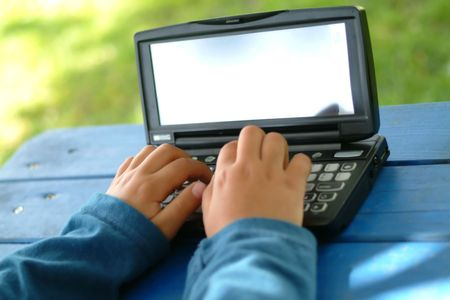 child typing and writing with a PDA