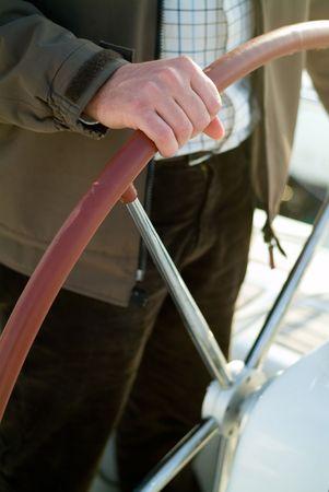 a man driving a rudder wheel of a yatch