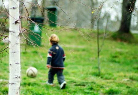 a boy playing soccer in the forest
