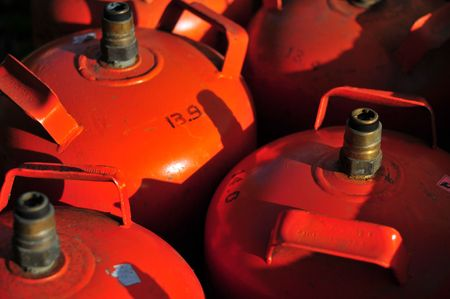 butane: old orange butane cylinders Stock Photo