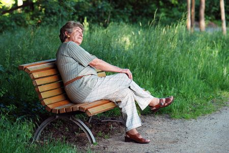 absent: Old lady on park bench Stock Photo