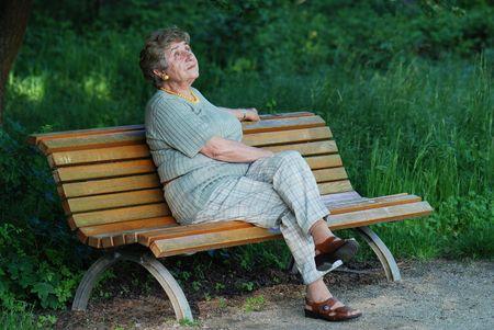 Oude dame op bankje  Stockfoto