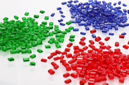 plastic: red, blue and green transparent polymer resin for injection molding on white