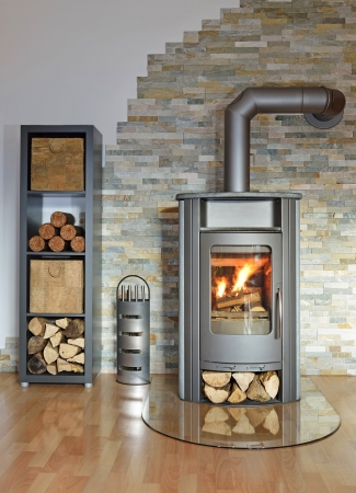 burning wood fired stove with fire-irons and fire-wood  Stock Photo
