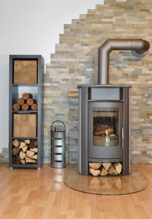hearthside: Wood fired stove with fire-wood and fire irons