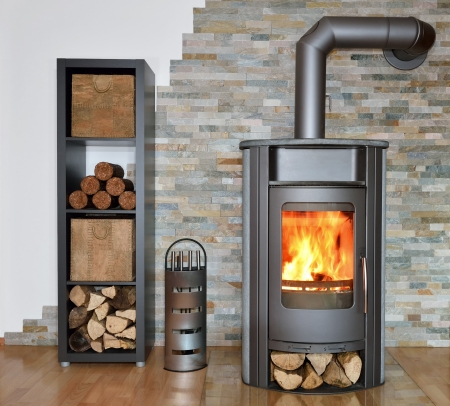 cosy: wood fired stove with fire-wood, fire-irons, and briquettes from bark