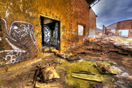 old abandoned factory plant with chemical substances at the ground and grafitti at brick walls
