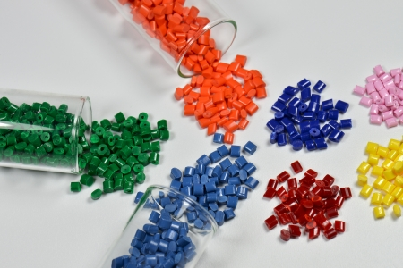 compounding: several dyed plastic granulates in test tubes on white table