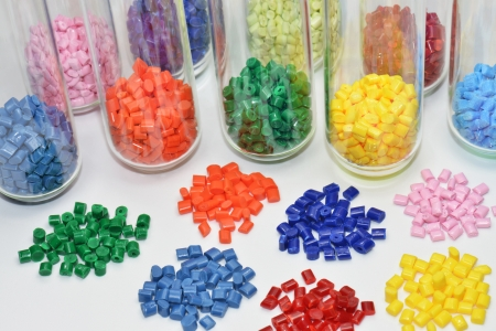 scrutinise: colored polymer resins in test tubes and on white table in lab